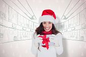 Festive brunette in santa hat holding gift against maroon christmas tree pattern
