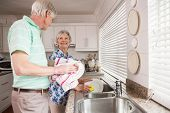 Senior couple washing the dishes at home in the kitchen