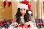 Surprised brunette opening gift bag at chistmas against fir tree forest and snowflakes