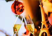 Champagne Flutes With Golden Bubbles On Christmas Eiffel Decoration Background