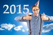 Geeky hipster wearing party hat smiling at camera against cloudy sky with sunshine