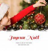 Festive little girl hanging a christmas decoration against joyeux noel