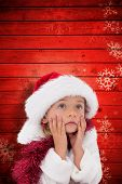 Cute little girl wearing santa hat and tinsel against snowflake pattern on red planks
