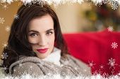 Serious brunette relaxing on the couch at christmas against fir tree forest and snowflakes Serious brunette relaxing on the couch at christmas at home in the living room