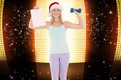 Festive fit blonde holding page and dumbbell against glittering screen on black background
