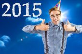 Geeky hipster wearing party hat smiling at camera against bright blue sky with clouds