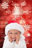 Cute little girl wearing santa hat against snowflake pattern on red planks