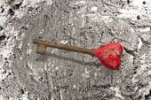 foto of ashes  - Old rusty iron key on grey ash background - JPG