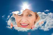 Older woman looking through rip against blue sky with clouds and sun