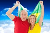 Happy older couple cheering at camera holding brazil flag against bright blue sky with clouds