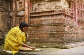 Woman sorts corn at Pancharatna Govinda temple Puthia, Bangladesh.