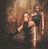 Attractive steampunk girl sitting on barrel