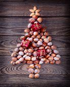 stock photo of hazelnut tree  - Christmas tree made of hazelnuts with red gifts on wooden background - JPG