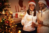 Santa man and woman with champagne looking at Bengal light on xmas night
