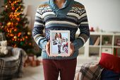 Young man showing image of his girlfriend holding touchpad with photo of him