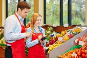 Young woman doing apprenticeship in supermarket getting help from store manager
