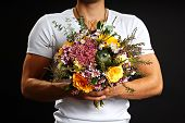 Man holds bouquet of flowers