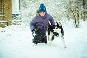Little boy with Husky dog on the snow