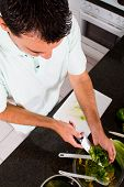 stock photo of chef knife  - a vegetarian man preparing vegetables in the kitchen - JPG