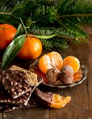 image of tangerine-tree  - Chocolate truffles and tangerines with fir tree branches on a wooden table - JPG