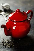 Tea composition with red teapot on dark background