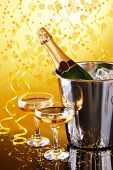 Bottle of champagne in bucket with ice and glasses of champagne, on bright background