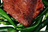 meaty food : roast meat steak on green hot chili peppers on a white background