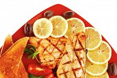 grilled salmon and lemon on red plate