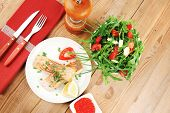 healthy sea food : roasted pink salmon fillet with vegetable salad , chives, lemon, red caviar in white bowl, with pepper in grinder and cutlery on white dish over wooden table