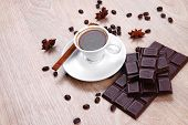 sweet hot drink : black Turkish coffee in small white mug with coffee beans spilled over a wooden table with stripes of dark chocolate and cinnamon stick