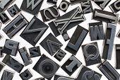 random letters in vintage letterpress metal type against white background