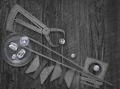 black and white image of a vintage jeweler tools and diamonds over wooden bench, space for text