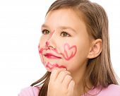Little girl is applying lipstick on her cheek, nose and chin, isolated over white