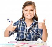 Girl is writing on color stickers using pen, planning concept, self-organization, showing thumb up sign, isolated over white