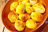 Potatoes fried in ceramic pan on board
