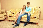 Romantic young couple sitting relaxed on a sofa in the cozy living room of their home.