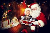 Santa Claus and happy boy sitting in Christmas room and reading a book. Christmas home decor.