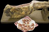 Side view of Serrano ham leg and plate with slices over black