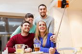 people, leisure, friendship and technology concept - group of happy friends with smartphone selfie stick taking picture and drinking tea at cafe