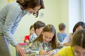 education, elementary school, learning and people concept - teacher helping school girl writing test in classroom