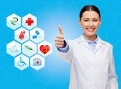 healthcare, medicine, people, gesture and symbols concept - smiling young female doctor or nurse showing thumbs up over medical icons and blue background