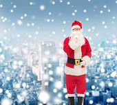 christmas, holidays and people concept - man in costume of santa claus making hush gesture over snowy city background