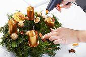 Woman Attaches Cinnamon On A Christmas Wreath