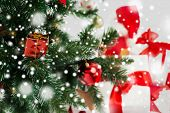 holidays, winter and celebration concept - close up of christmas tree and presents over gray background with snow