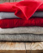 Stack Of Women's Sweaters In Grey And Red Colors