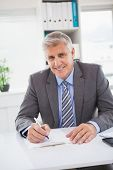 Smiling businessman writing on clipboard in his office