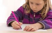Little girl busy with drawing