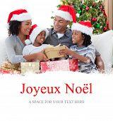 Family celebrating Christmas at home against joyeux noel