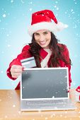 Festive brunette shopping online against blue background with vignette
