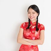 Portrait of Asian Chinese girl smiling, in traditional red qipao standing on plain background.